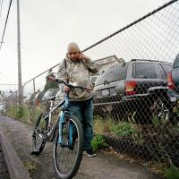 Man with bike talking on phone SE 82nd Ave