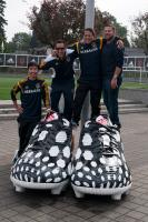Soccer players standing on very large soccer shoes