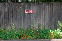 fence with parking sign and flowers