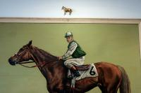 painting of horse racer, with a brass horse above
