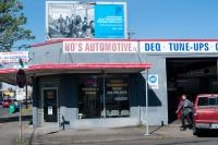 person outside auto shop with sign above