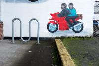bike rack and painting of two people riding a motor cycle