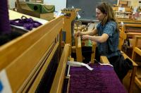 person weaving on a loom inside the Multnomah Arts Center