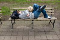 person resting on a park bench with a basketball