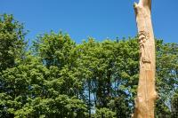 log pole with face carved on it