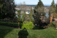 looking down through a terraced yard at a ship in the Willamette River