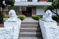 two white lion statues outside a house