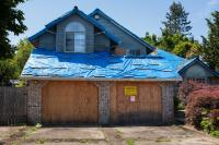 empty fire damaged house with blue plastic traps on the roof.