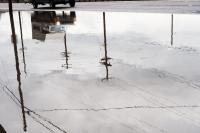 reflection of a truck and power poles in a large puddle