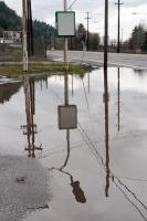 reflection of sign and power poles in a large puddle