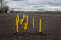 yellow poles and vents sticking out of gravel