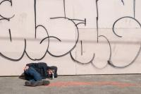 man pasted out under some graffiti