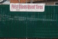 Green fence with a sign that reads First Class Used Tires
