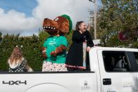 Woman in the back of a truck with someone in a dog costume.