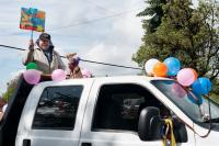 Man standing in the back of a truck with a small dog, some balloons and a sign.