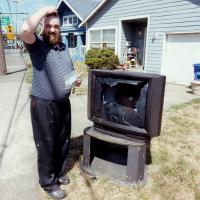 Man scratching his head in front of broken TV